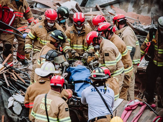Firefighters rescue a woman from a collapsed building