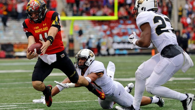 Maryland quarterback Perry Hills, left, leaps for a first down as he is chased by Purdue linebacker Markus Bailey, center, and safety Navon Mosley in the first half of an NCAA college football game in College Park, Md., Saturday, Oct. 1, 2016. (AP Photo/Patrick Semansky)