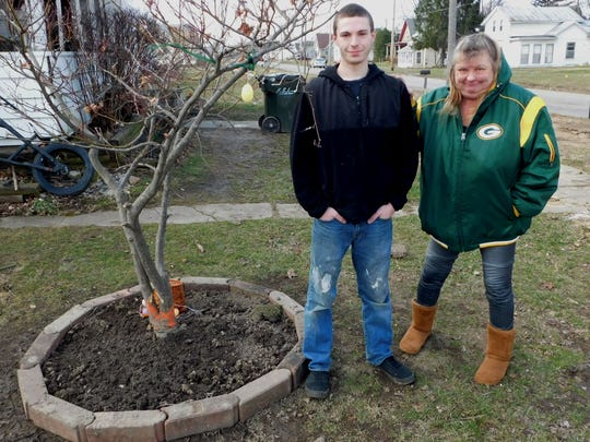 Rhonda Van Fleet, right, said she was very emotional about the sugar maple in front of her house being cut down. Her son, Robert Mann, 20, helped save a Japanese miniature maple from the axe by moving it into the family yard.