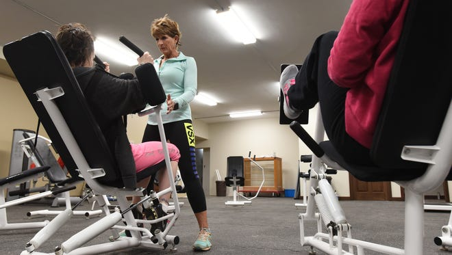 Trainer Polly Pletcher works with a woman at the Perry Behavioral Health Choices gymnasium in New Lexington recently. The new facility is housed in the PBHC Activity Center on Main Street.