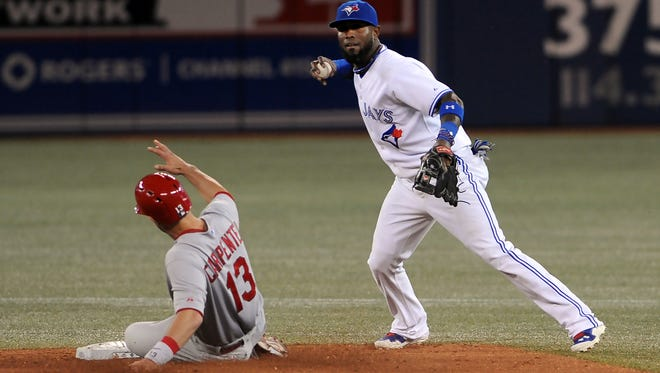 Toronto Blue Jays shortstop Jose Reyes is unable to complete a double play after forcing out St. Louis Cardinals third baseman Matt Carpenter in the seventh inning at Rogers Centre.