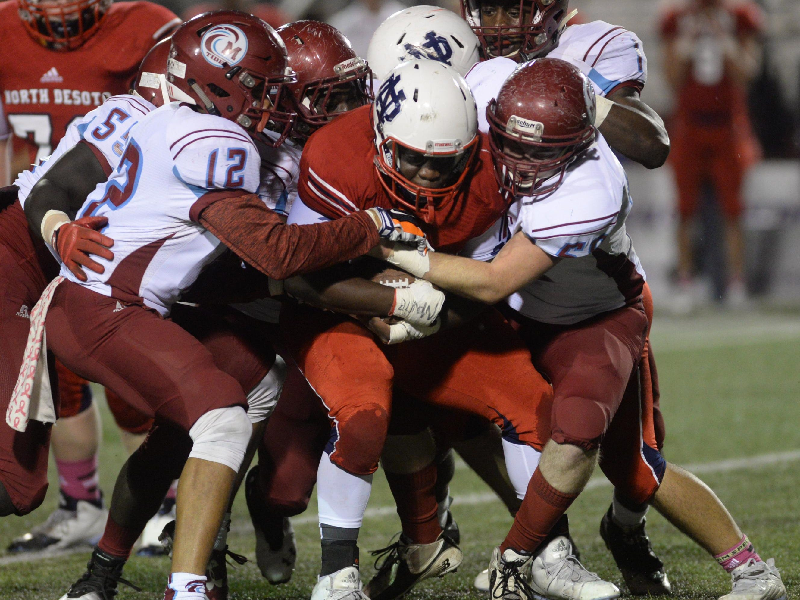 The Minden defense smothers Dennis Hall of North Desoto during their game Friday night.