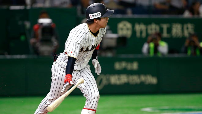 Japan's designated hitter Tetsuto Yamada watches the flight of his two-run home-run off Cuba's pitcher Miguel Lahera.