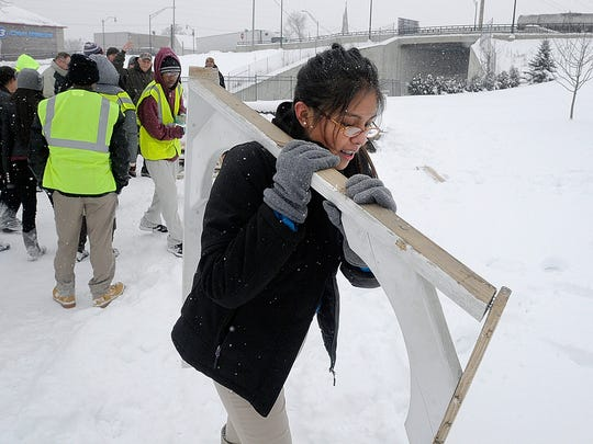 In this Feb. 3, 2015 photo, Jaremy Hernandez, a junior at Kankakee High School in Kankakee, Ill., carries a large piece of a gazebo from a park after students dismantled the structure. After Places Rated Almanac called Kankakee the worst metropolitan area to live in the U.S. and Canada in 1999, late night talk-show host David Letterman poked fun with a Top 10 list and sent two gazebos to Kankakee to spruce things up. Now students are dismantling the gazebos and making a commemorative rocking chair out of the wood for Letterman's retirement. (AP Photo/The Daily Journal, Mike Voss)