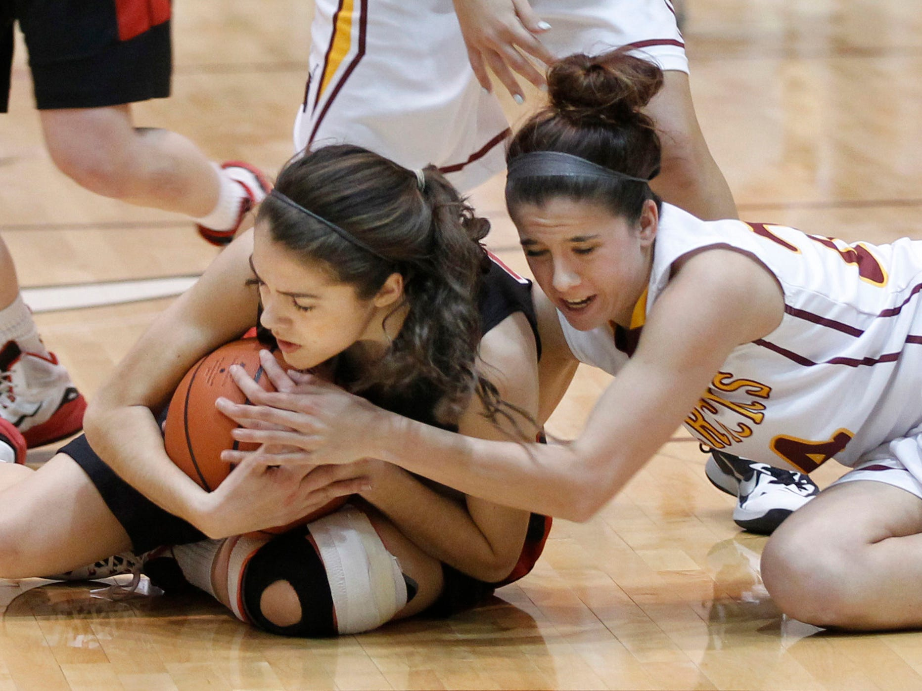 Allie Eavey, left, of Lafayette Jeff and McCutcheon's Kerstyn Lowery wrestle for control of the ball in girls sectional basketball action Friday, February 13, 2015, at McCutcheon High School. McCutcheon defeated Lafayette Jeff 43-33.