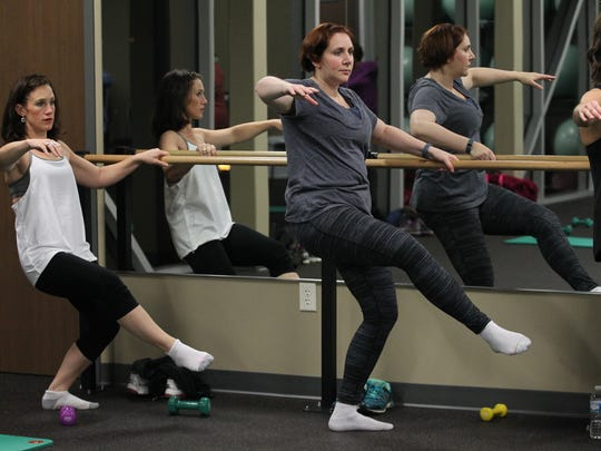Carrie Hutton, left, and Laura Scudiere participate in a barre class Nov. 6 at the Woodson YMCA in Wausau, Thursday, November 6, 2014.