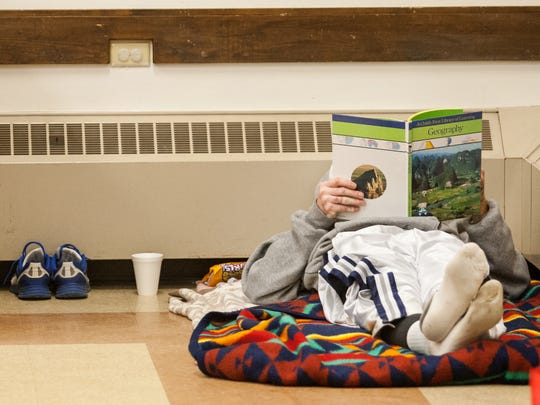 A homeless man reads a book after making his bed at St. Paul's Lutheran Church's code purple shelter in 2014.
