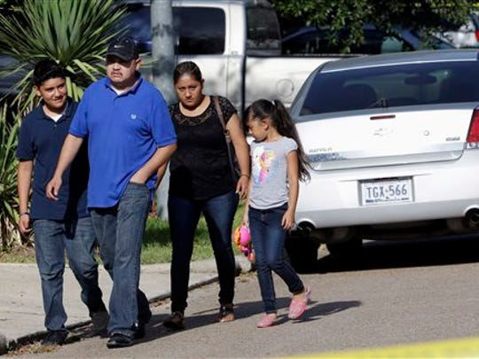 Neighbors leave the scene of multiple fatalities found in a home on their street Sunday, Aug. 9, 2015, in Houston. Eight people, including five children and three adults, were found dead inside a Houston-area home following the arrest of a man who exchanged gunfire with police, Texas authorities said Sunday.