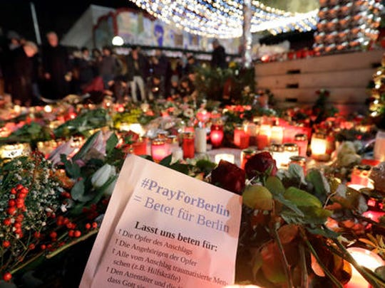People stay in front of candles close to a Christmas market beside the memorial church in Berlin, Germany, Wednesday, Dec. 21, 2016, two days after a truck ran into a crowded Christmas market and killed several people.