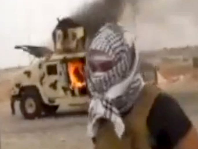 An image made from an Iraqi0Revolution video shows a militant standing in front of a burning Iraqi army Humvee in Tikrit.