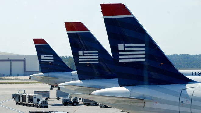 Tails of US Airways jets are seen in Charlotte on Sept. 27, 2012.