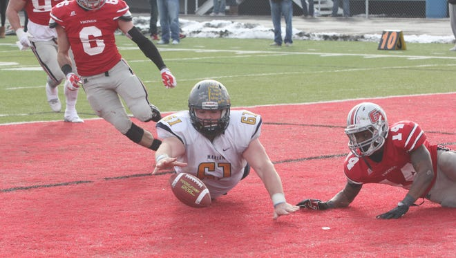 Marian center Zach Mitchell recovers a fumble in the end zone for a touchdown as the Knights knocked defending national champs Grand View out of the playoffs on Saturday.