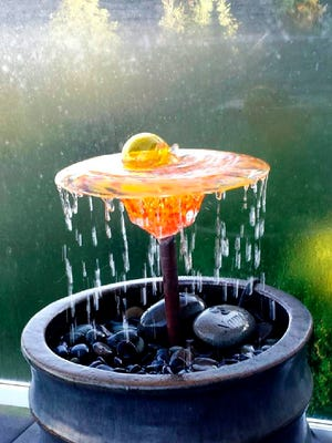 This photo provided by Glass Gardens NW shows a glass fountain by Seattle area glass blower Barbara Sanderson, who crafts beautiful flowers, fountains and sculptures that can be placed in gardens and water features. They bring an element of fantasy to an outdoor space in a unique and artful way.
