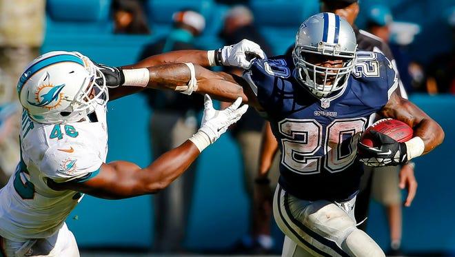 Dallas Cowboys running back Darren McFadden (20) stiff arms Miami Dolphins linebacker Neville Hewitt (46) during the second half at Sun Life Stadium. The Cowboys won 24-14.