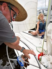 Jackson Yacht Club member John Wakeland, left, helps
