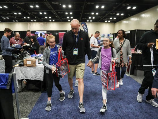 Louisville basketball coach Chris Mack holds the hand of daughter Hailee as other daughter Lainee walks next to him at the National Association of Basketball Coaches conference in San Antonio March 30, 2018, the day before the start of the Final Four.