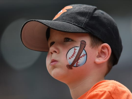 "FILE - In this Aug. 6, 2017, file photo, a young baseball fan looks on before the Baltimore Orioles and Detroit Tigers baseball game, in Baltimore. The Orioles have launched a program that will enable kids to attend home games this season free of charge. Fulfilling a child's request to ""take me out to the ballpark"" has become a lot cheaper at Camden Yards. Every adult who purchases a regularly-priced upper deck ticket can bring up to two children, age 9 or under. (AP Photo/Gail Burton, File)"