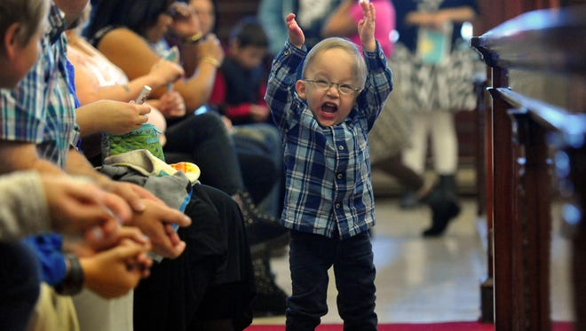 Aidyn Mee plays in the gallery of Judge Pinski's courtroom before Thursday's adoption ceremony where 27 adoptions were finalized, one the largest ceremonies ever held in Great Falls.