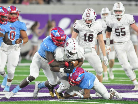 Hirschi defensive lineman Ezekiel Holmes, center left, and a teammate tackle Brownwood running back Gavin Jefferson during the Huskies' 44-34 win in a Region I-4A bi-district playoff Friday at Abilene Christian University's Wildcat Stadium..