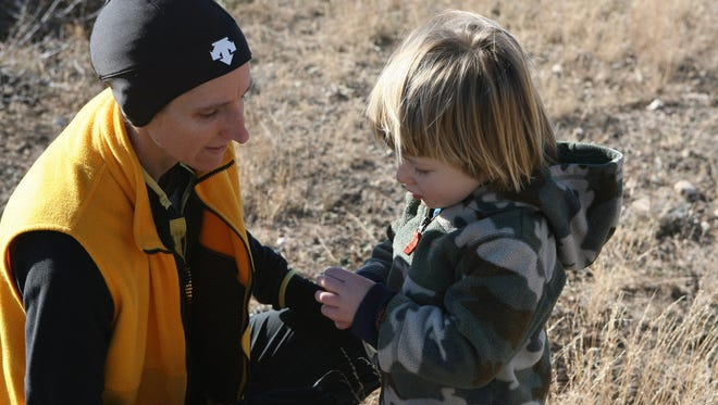 Jessie Kaven, 41, helps her son Cody Kaven, 2, open a packet of string cheese as they take a break during the San Angelo State Park first day hike in 2014.