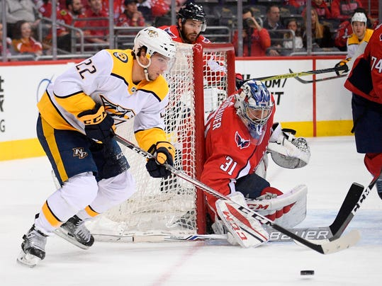 Nashville Predators left wing Kevin Fiala (22) skates with the puck next to Washington Capitals goaltender Philipp Grubauer (31) during the first period of an NHL hockey game Thursday, April 5, 2018, in Washington. (AP Photo/Nick Wass)