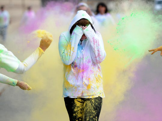 A participant covers her face as she crosse the finish line during last year's Color Their Legacy 5K Run/Walk at Greenwood High School.