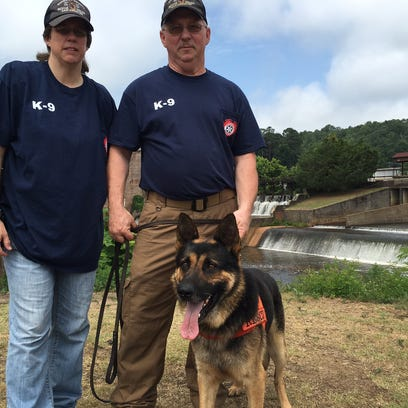 Sherry and Fabian Mann pose with Remi, the search dog