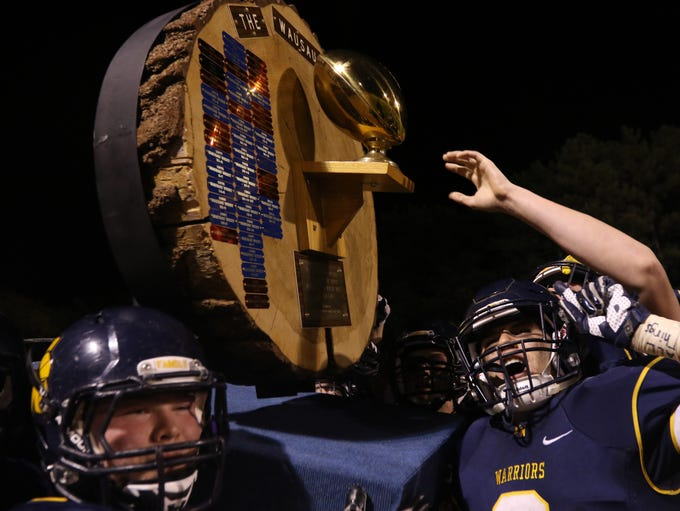 Wausau West players celebrate their win by hoisting