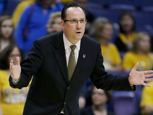 Wichita State head coach Gregg Marshall makes a call from the sideline against Cal Poly during the first half of a second-round game in the NCAA college basketball tournament Friday, March 21, 2014, in St. Louis. (AP Photo/Jeff Roberson)