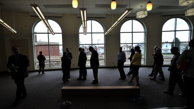 A tour group walks through the media center of Mount Pleasant Elementary School in Lancaster. The school will open to students at the beginning of the 2015-16 school year.