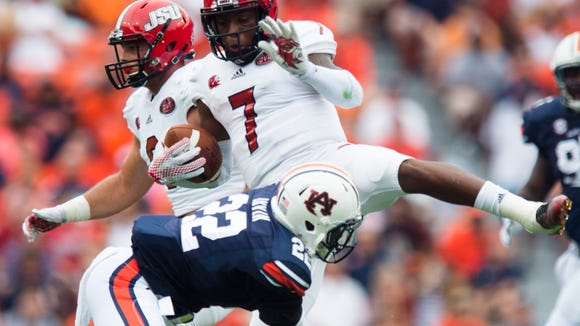 Jacksonville State Gamecocks quarterback Eli Jenkins (7) spins away from Auburn Tigers defensive back Tim Irvin (22) during the first half of the NCAA Auburn vs. Jacksonville State on Saturday, Sept. 12, 2015, in at Jordan-Hare Stadium in Auburn, Ala.