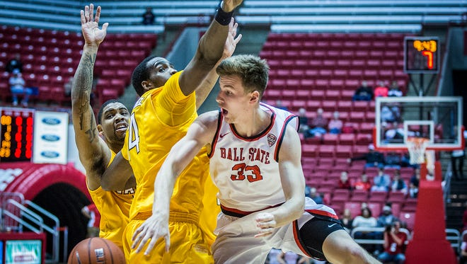 Ball State's Ryan Weber passes past Valparaiso's defense during their game at Worthen Arena Saturday, Nov. 28, 2015.