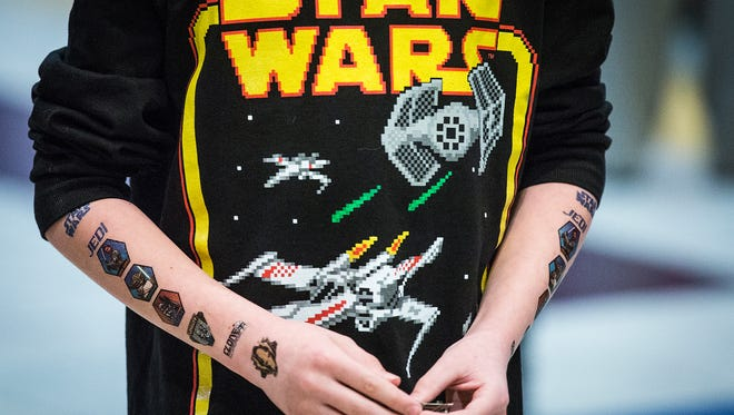 A child shows off temporary Star Wars tattoos while waiting in line for Episode VII at AMC Showplace Muncie 12 Thursday night.