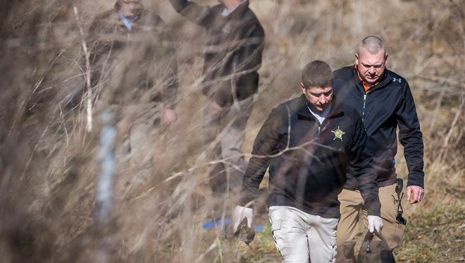 Investigators work at the scene of a shooting in a field near 4024 S. Burlington Dr. Tuesday afternoon. The body of the male victim was found by the driver of a construction vehicle who was doing work on the property.