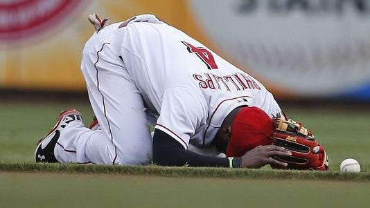 Cincinnati Reds second baseman Brandon Phillips (4) holds his head as he bobbled a ball after making a diving stop of a sharp hit off the bat of Toronto Blue Jays third baseman Brett Lawrie.