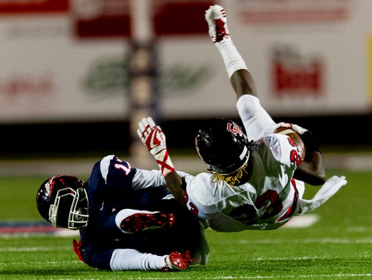 Central's Trey'Sean Moore (23) is tackled by South-Doyle's