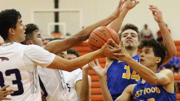 Eastlake's Joseph Maldonado left, and Mitchell Martinez, 42, of Eastwood join in the battle for a rebound under Eastwood's basket Tuesday night at Eastlake. The Falcons defeated the Troopers 66-62.