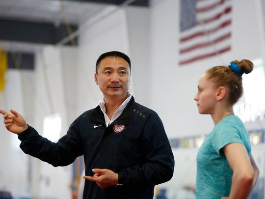 Coach Liang Chow works with Rachel Gowey and some of his other elite gymnasts Thursday, May 12, 2016, at Chow's Gymnastics and Dance in West Des Moines.