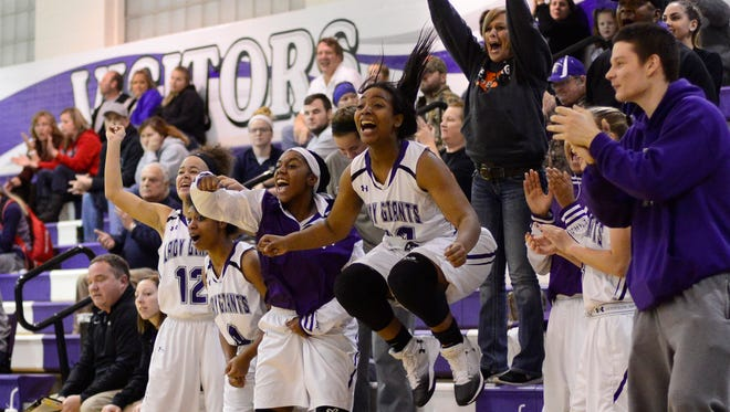Ahlia Simms leaps in the air as the players on Fremont Ross's bench celebrate against Marion Harding.