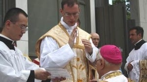 Father Kenneth Walker gives a first blessing to Bishop Bruskewitz after Walker's ordination May 19, 2012, at Cathedral of the Risen Christ in Lincoln, Neb.
