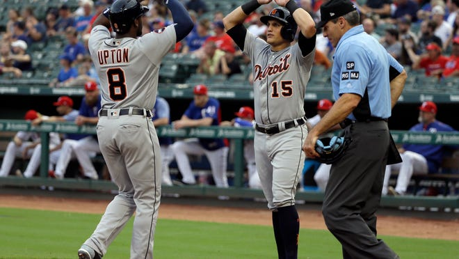 Detroit Tigers' Justin Upton (8) and Mikie Mahtook (15) celebrate Upton's two-run home run that scored them as umpire Angel Hernandez stands by the plate in the first inning of a baseball game against the Texas Rangers, Monday, Aug. 14, 2017, in Arlington, Texas. (AP Photo/Tony Gutierrez)