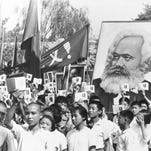 In this Sept. 14, 1966 file photo, youths are seen at a rally during the height of the Red Guard upheaval waving copies of the collected writings of Communist Party Chairman Mao Zedong, often referred to as Mao's Little Red Book and carrying a poster of Karl Marx.