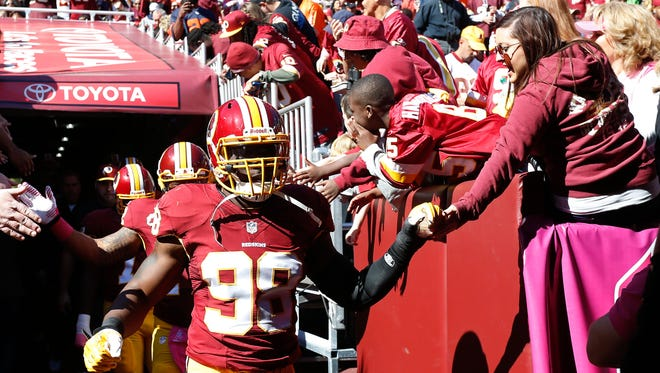 Washington Redskins outside linebacker Brian Orakpo (98) shakes hands with fans while walking onto the field prior to the Redskins game against the Chicago Bears at FedEx Field.