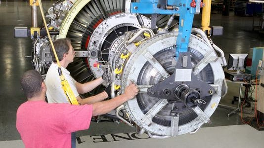 Engine assemblers DeJuan Blumberg and Keith Langevin join the core of a CFM56-7 engine to the fan at GE Aviation's Evendale plant.