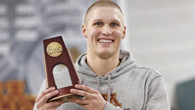 Sevastopol grad Conner McHugh holds his all-America trophy after competing at the NCAA national swim meet.