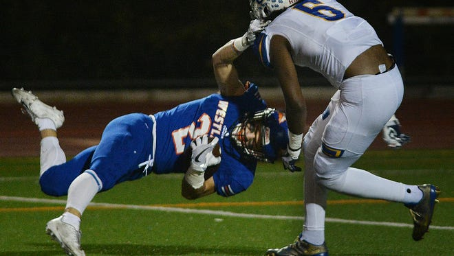 Westlake's Jason Heller is tackled by Charter Oak's Jermaine Braddock after catching a pass during Friday night's Division 3 quarterfinal game at Westlake High. Charter Oak won 39-28.
