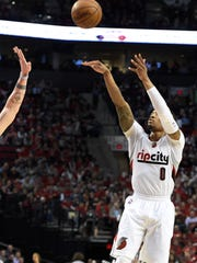 Portland Trail Blazers guard Damian Lillard (0) hits a 3-point shot the during the second half of an NBA basketball game against the Denver Nuggets in Portland, Ore., Wednesday, April 13, 2016. The Blazers won 107-99.