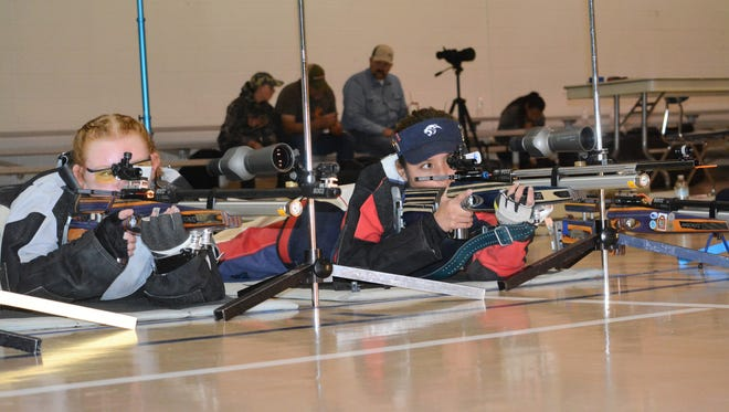 Piedra Vista rifle team members Amoret McCartney, left, and Josephine John zone in on square targets during the second day of the Civilian Marksmanship Program Clinic Saturday at the high school.