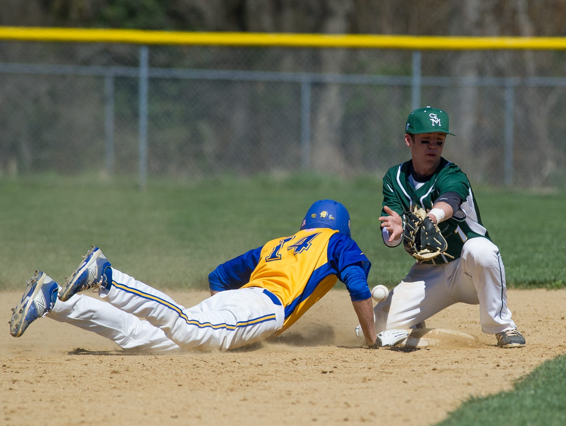 Caesar Rodney's Thomas Pomatto (14) is hit by the ball at second base as St. Mark's John Panico (12) tries to catch the ball.