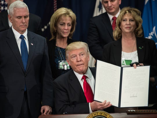 President Trump holds up an executive order fpr immigration